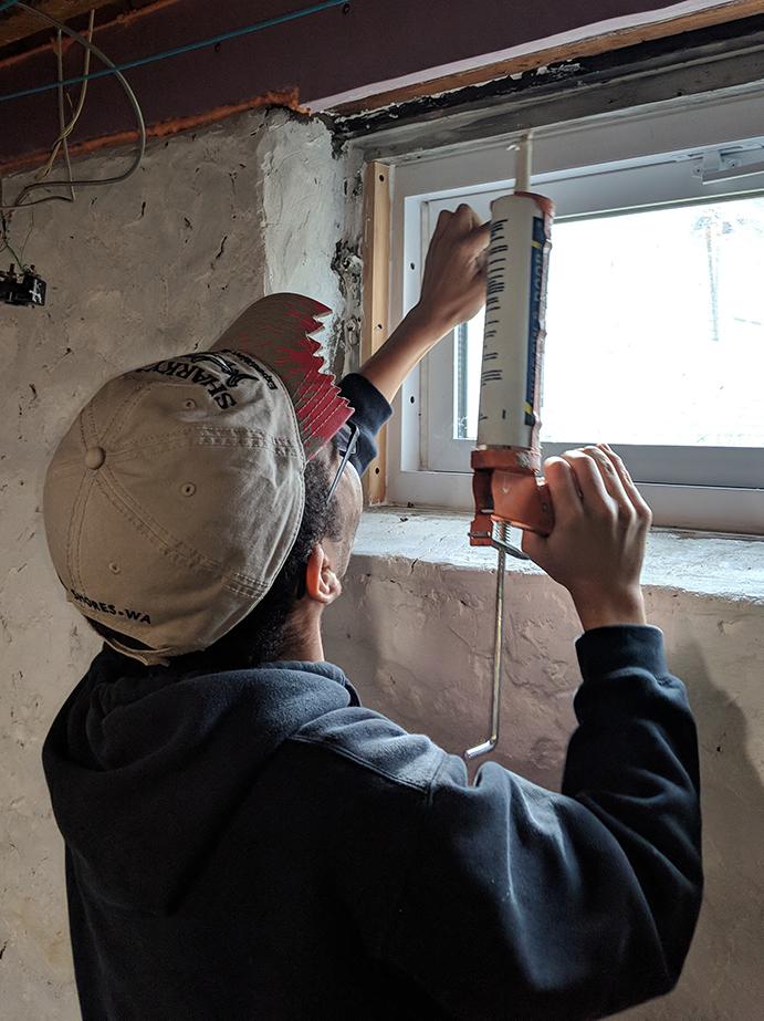 Volunteer caulks window in house