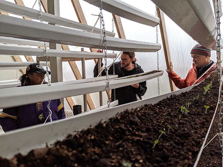 Community members tour the Deep Winter Greenhouse at the Denfeld Food Forest.