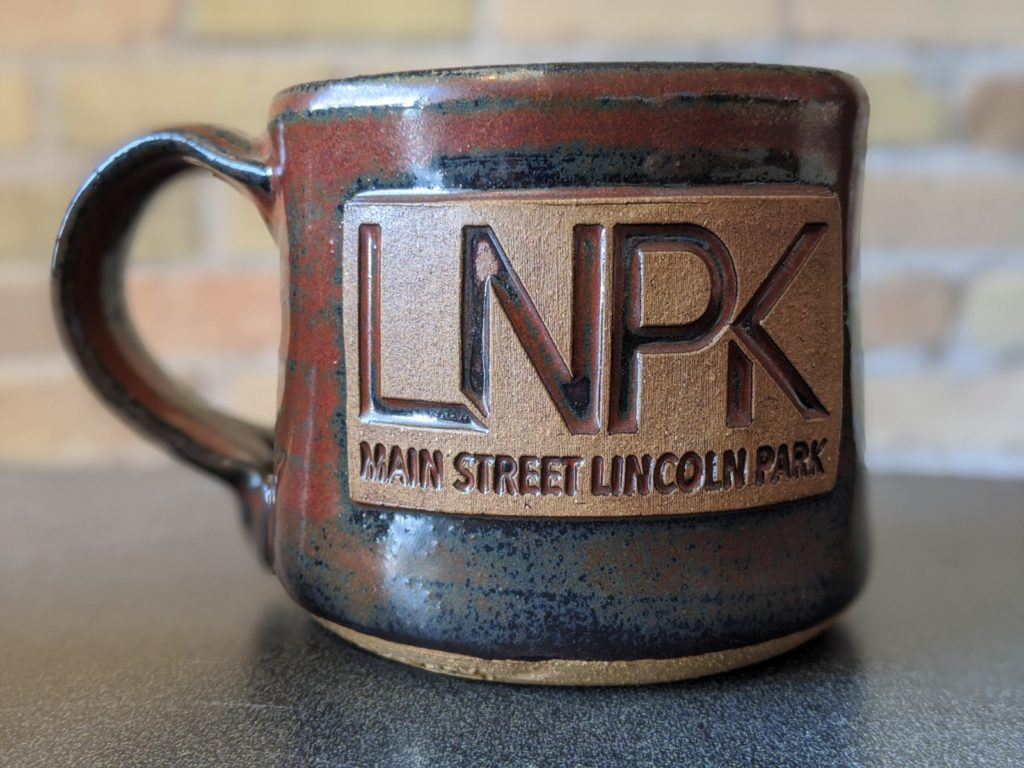 Duluth Pottery mug with Main Street Lincoln Park logo stamped on it.